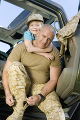 Boy 5-6 embracing military father in vehicle, portrait