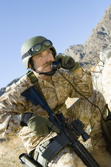 Soldier using field phone in mountains