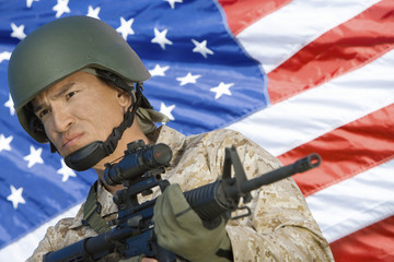 Soldier holding rifle in front of United States flag, portrait