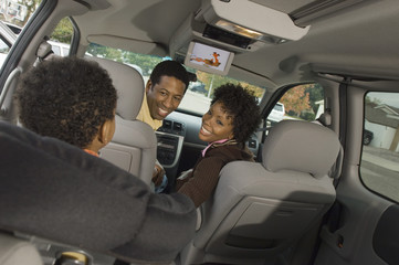 Couple smiling at young son in car