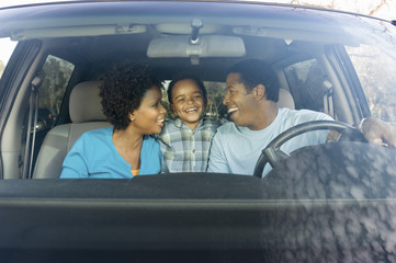 Couple smiling at young son in car, view through windscreen