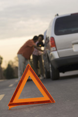 Young couple leaning on car behind warning triangle