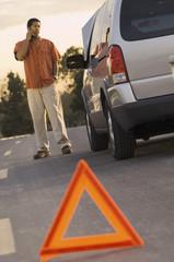Young man looking at car behind warning triangle