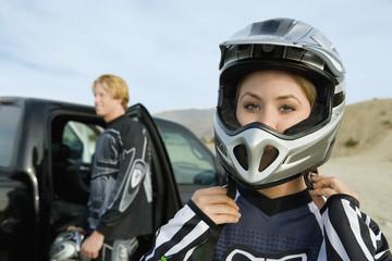 Female motocross racer fastening helmet
