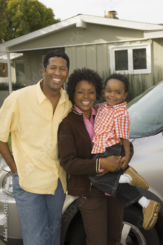 Couple with young boy standing by car in front of bungalow