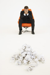 Frustrated businessman sitting near pile of crumpled paper