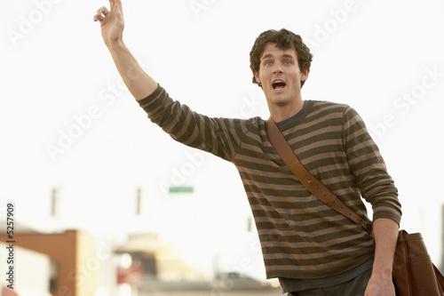 Man signalling taxi in street