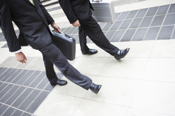 Two businessmen walking with briefcases, low section