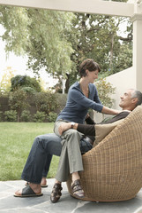 Woman sitting on husband's laps on patio