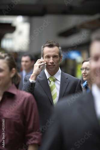 Businessman using mobile phone among crowd in station