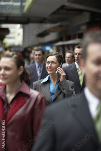 Businesswoman using mobile phone among crowd in station