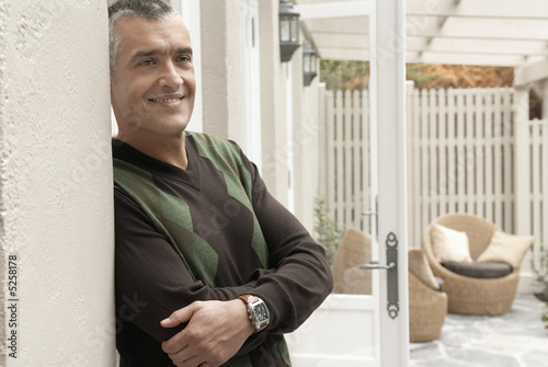 Smiling man standing at patio doors