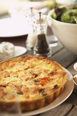 Plate of Quiche setting on picnic table among other dishes