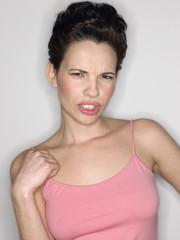 Woman gritting teeth in studio half-length