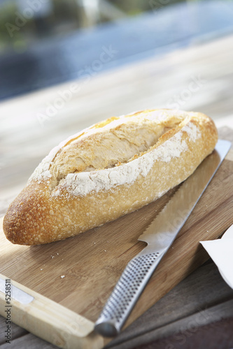 Bread Roll on cutting board on picnic table with bread knife