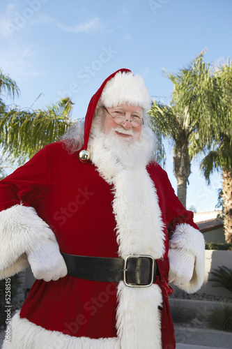 Smiling Santa Claus standing outside With Palm Trees