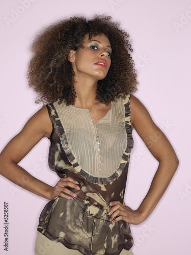 Woman with curly hair and hands on hips in studio