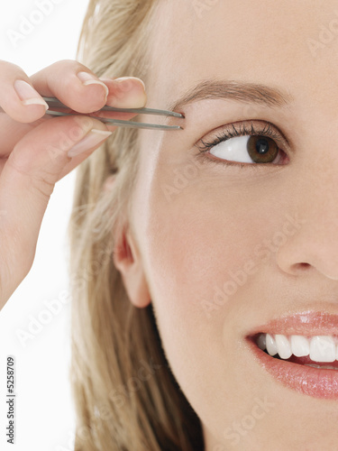 Young Woman Tweezing Eyebrows