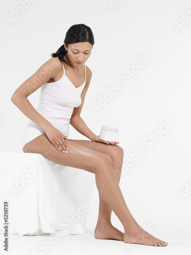 Young Woman Applying Body Lotion