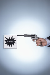 Man firing pistol with bang flag, close-up of hand