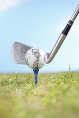 Golf club hitting golf ball with hundred-dollar logo on tee, close-up