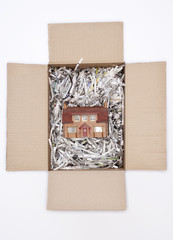 Model house in packing carton with shredded paper, view from above