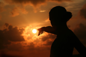 Young woman points out the sun