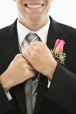 Groom adjusting his tie. poster