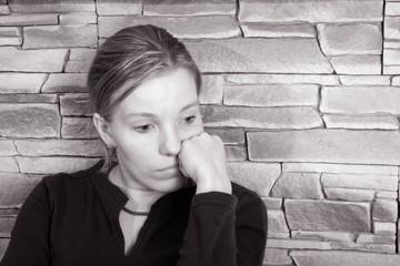 Girl sitting against a brick wall
