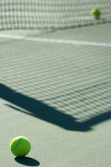 Tennis ball with net shadow and white line..