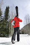Teenager carrying ski gear. poster