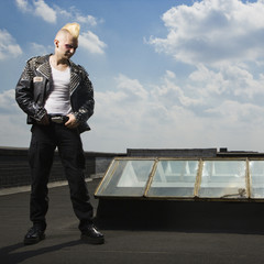 Punk standing on roof.