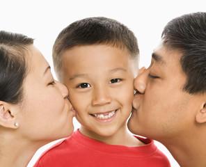 Parents kissing son.