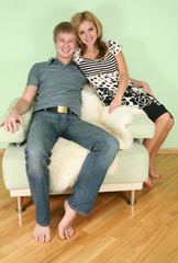 Young smiling couple on armchair