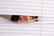 Woman peeking out from the blinds