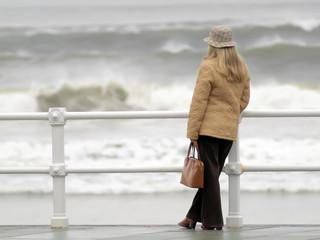 Mujer con sombrero mirando al mar