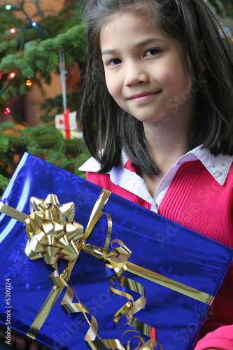 eight year old girl holding her christmas presents from jaren