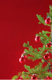 Small Christmas tree with red ornaments and red backdrop poster