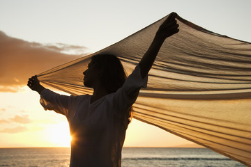 Woman holding up fabric silhouetted by sunset beside ocean.