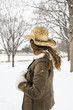 Brunette woman wearing straw cowboy hat in the snow.