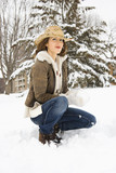 Female kneeling in snow with snowball wearing cowboy hat. poster