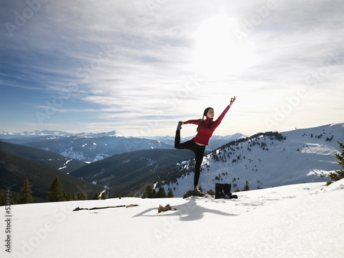 Woman doing yoga in snow.