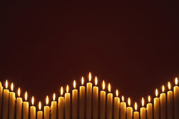 Row of lit candles, on black background