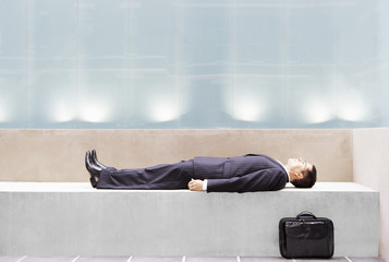 Businessman lying on concrete bench, side view