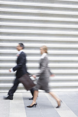 Businessman and businesswoman walking quickly, side view