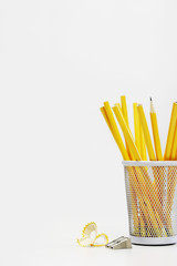 Group of yellow pencils in holder by sharpener