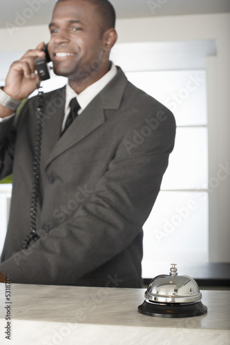 Businessman on phone at hotel reception desk