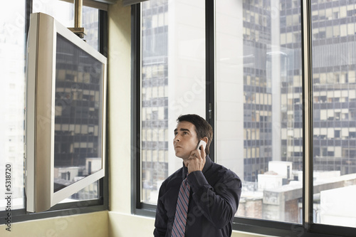 Businessman using cell phone looking at flat screen TV in office, half length