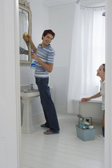 Couple cleaning bathroom