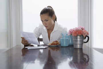 Woman reading at dining room table
